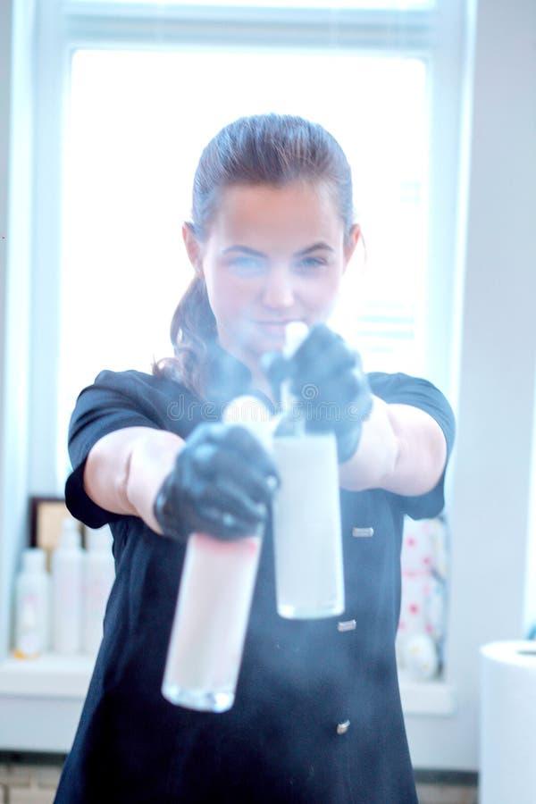 Kvinna i handskar och med antibacterial sprej royaltyfri foto