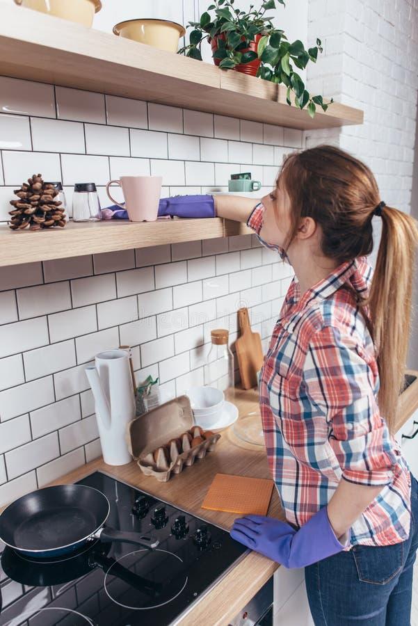 Kvinna i handskar som gör ren möblemang med hemmastatt kök för trasa arkivfoto