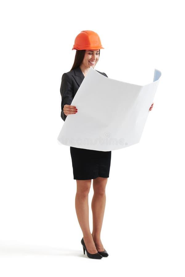 Kvinna i hardhaten som ser ritningen royaltyfri fotografi