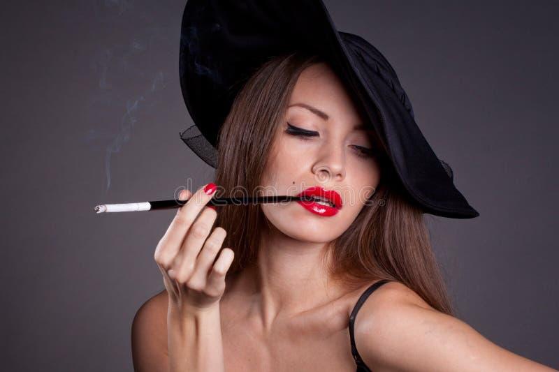 Kvinna i hatt med cigaretten arkivbilder
