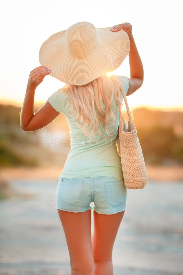 Kvinna i hatt med stora fält, på solnedgången arkivbild