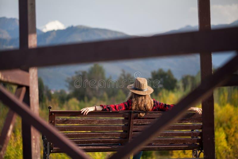 Kvinna i hatt på bänken royaltyfri bild