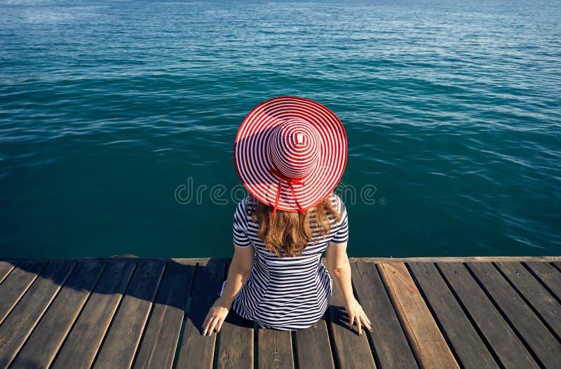 Kvinna i hatt på träpir arkivfoton