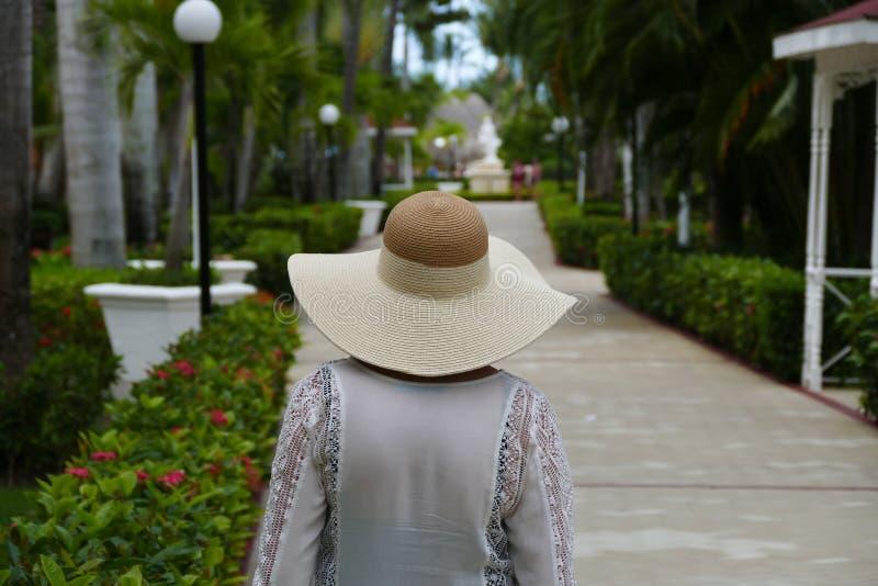 Kvinna i hatt som går i paradis på en härlig dag royaltyfri fotografi