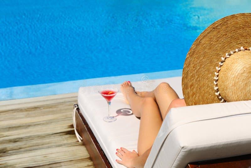 Kvinna på poolsiden med den kosmopolitiska coctailen royaltyfri fotografi
