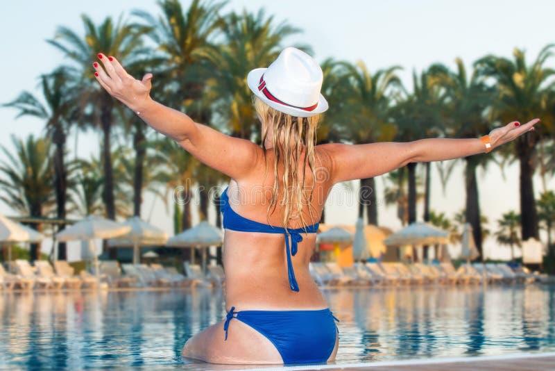 Kvinna i hatt som kopplar av på simbassängen Flicka på pölen för loppbrunnsortsemesterort Lyxig semester för sommar arkivfoto