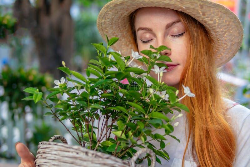 Kvinna i hatt som luktar växtblommor arkivfoton