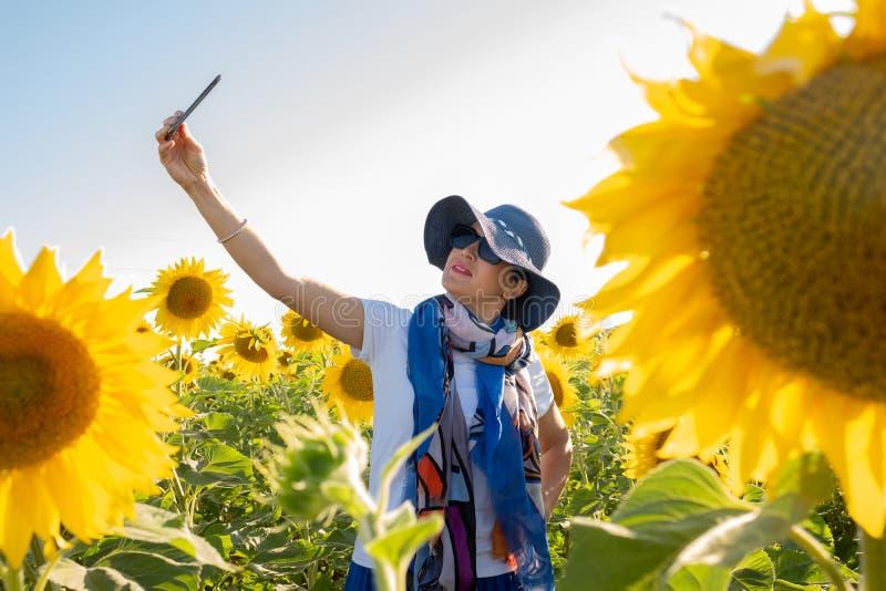 Kvinna i hatten som g?r en selfie i ett f?lt av solrosor royaltyfria bilder