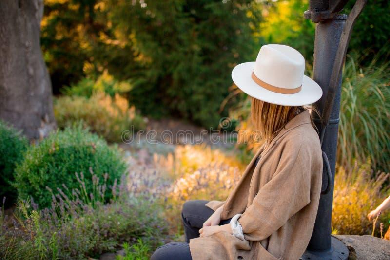 Kvinna i hatten som sitter nära lavendelblommor arkivfoton