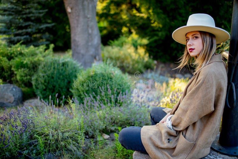 Kvinna i hatten som sitter nära lavendelblommor arkivbilder
