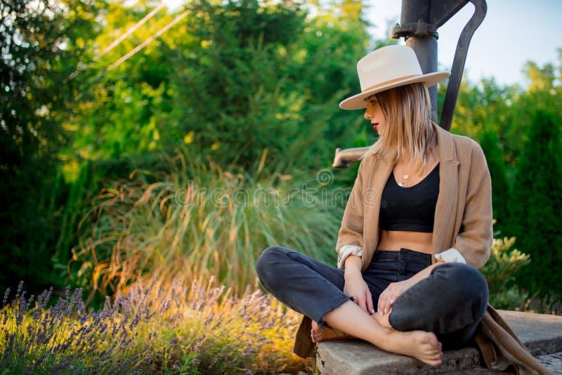 Kvinna i hatten som sitter nära lavendelblommor arkivfoto
