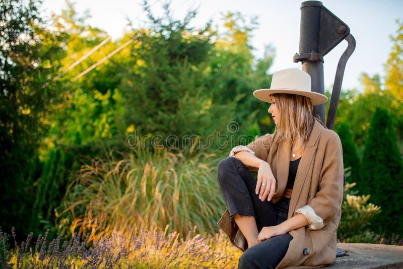 Kvinna i hatten som sitter nära lavendelblommor royaltyfri bild