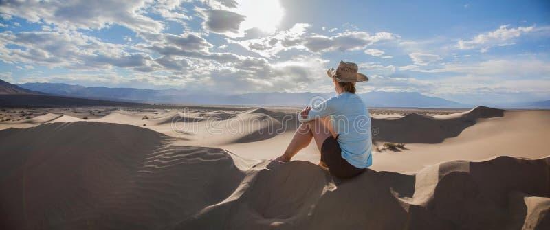 Kvinna i hatten som ut ser över dyerna för Mesquitelägenhetsand i den Death Valley nationalparken på solnedgången royaltyfri foto