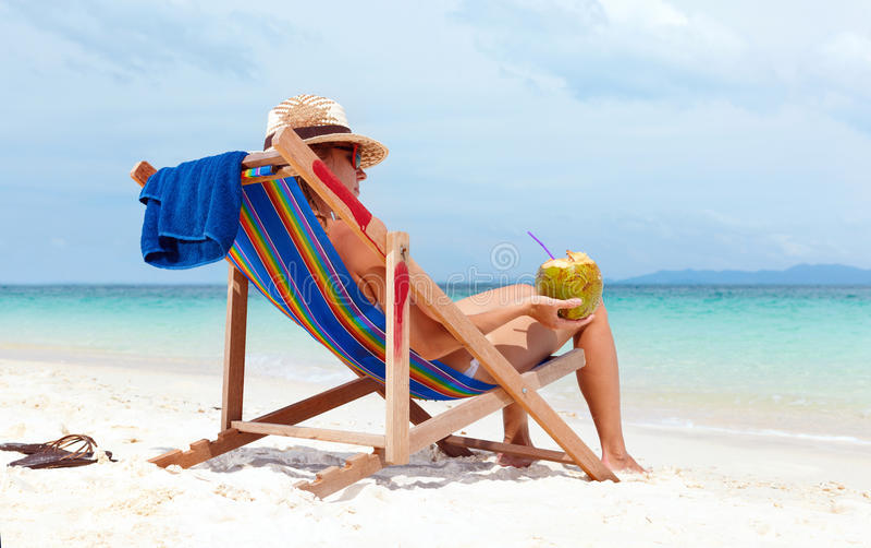 Kvinna i hattsammanträde på tropisk strand royaltyfri bild