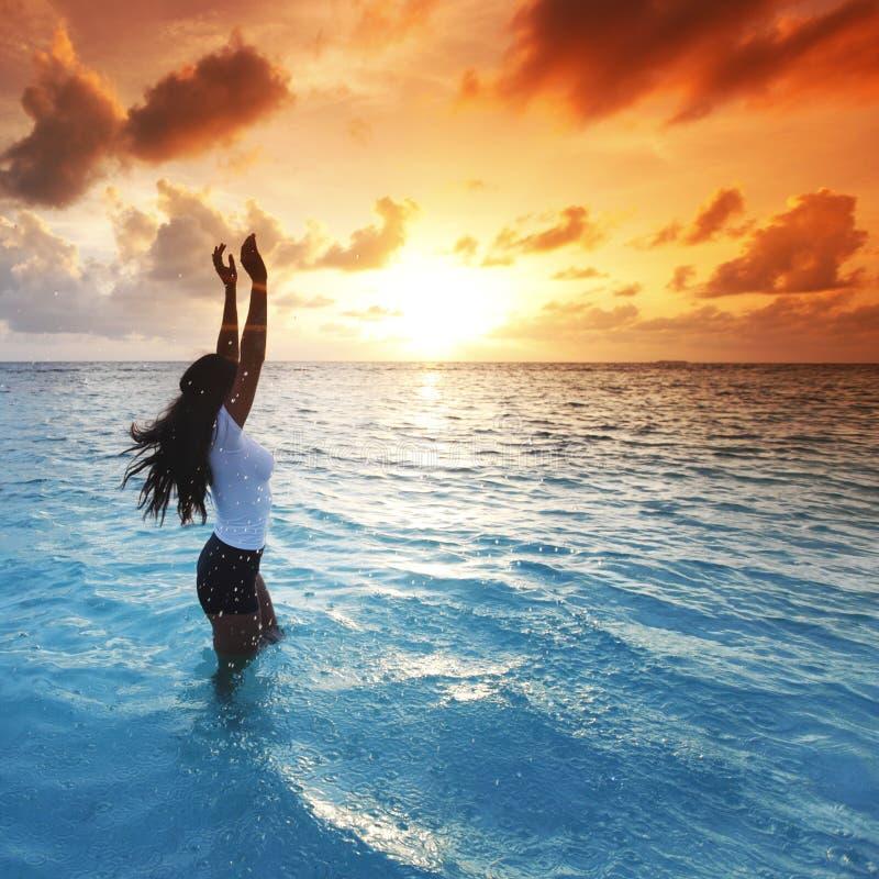 Kvinna i havet på solnedgång arkivbild