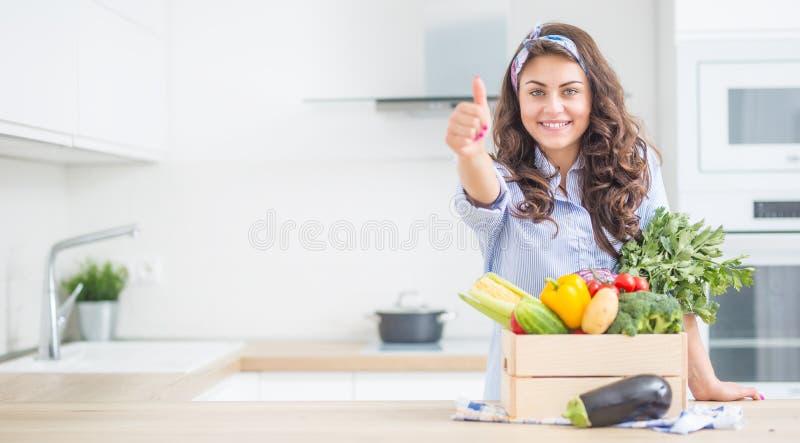 Kvinna i hennes kök med träasken mycket av den organiska grönsaken som visar upp tummar arkivfoton