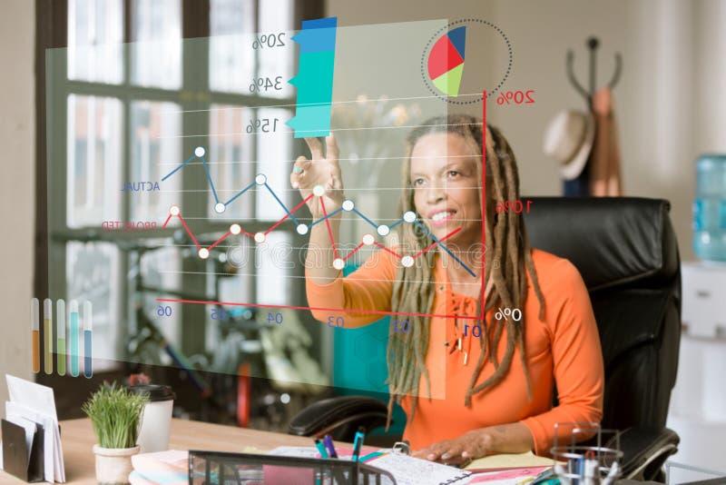 Kvinna i hennes kontor som tar fram information från en futuristiska Fina royaltyfri bild