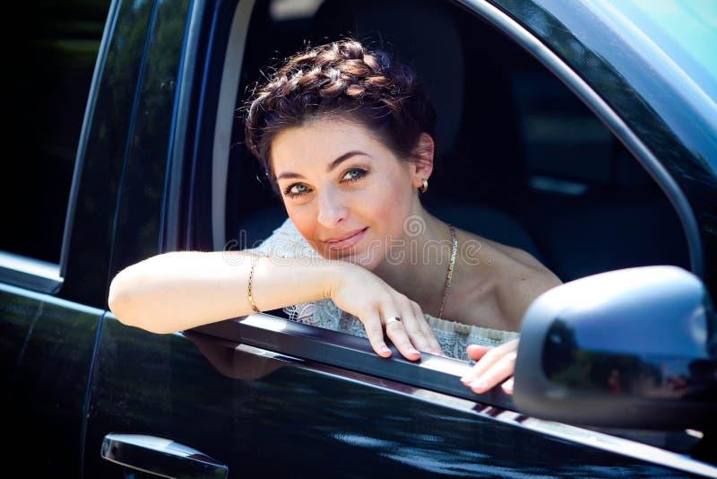 Kvinna i hennes le för bil royaltyfria foton
