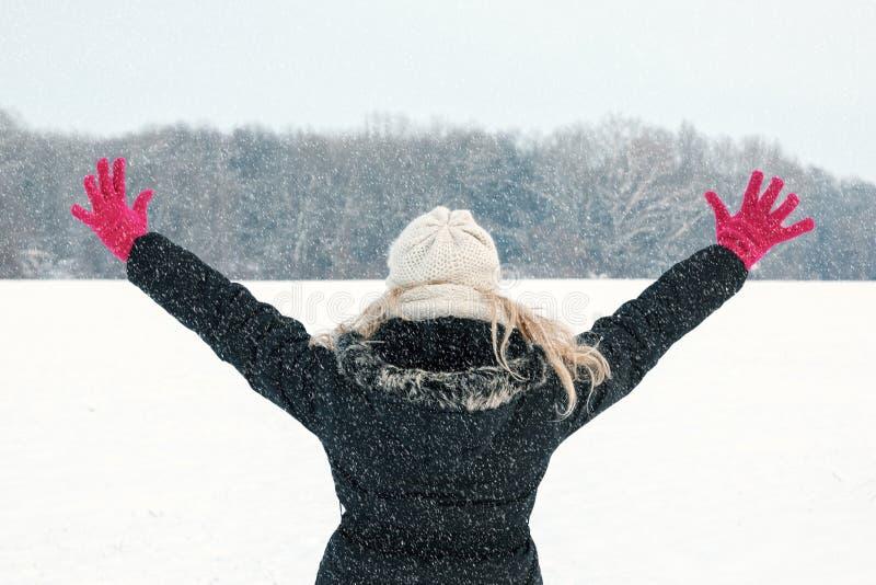 Kvinna, i hennes snöuppvisning tillbaka och att vända mot skogen med handrais arkivbild