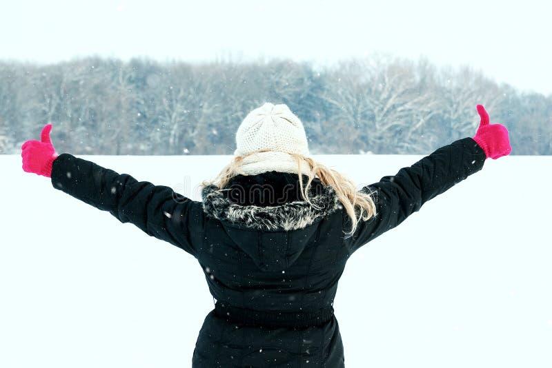 Kvinna, i hennes snöuppvisning tillbaka och att vända mot skogen med tummar upp royaltyfri foto
