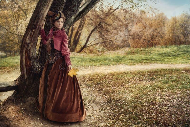 Kvinna i historisk klänning nära trädet i höstskog arkivbild