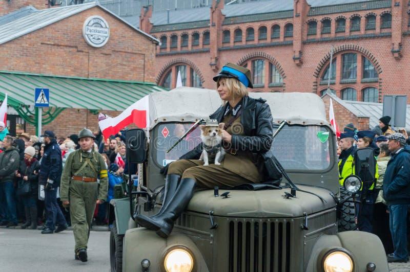 Kvinna i historisk soldatlikformig med hunden på bilen På 11 är November 2018 den 100. årsdagen av att återvinna independenc arkivbilder