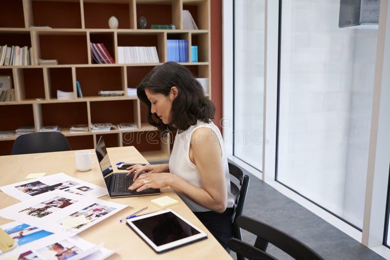 Kvinna i idérikt massmediakontor genom att använda bärbara datorn som är horisontal royaltyfria foton