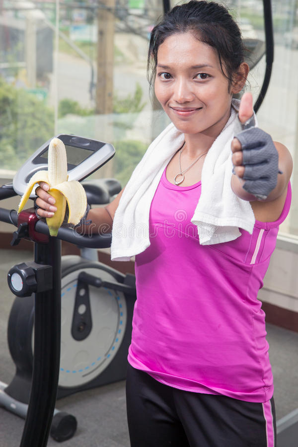 Kvinna i idrottshallen som äter en banan royaltyfri foto