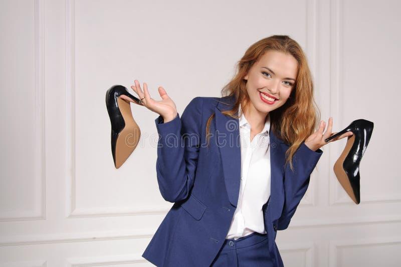 Kvinna i innehav för formella kläder i skor för varje hand royaltyfri bild