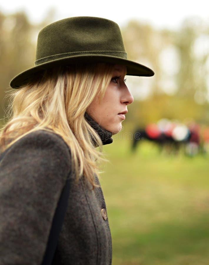 Kvinna i jakthatt med hästar i bakgrund royaltyfri foto