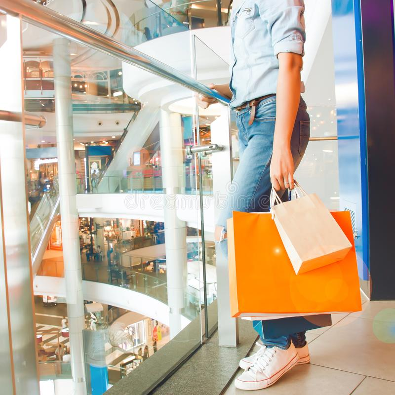 Kvinna i jeans som rymmer den conc shoppingpåsar, mode och livsstilen fotografering för bildbyråer