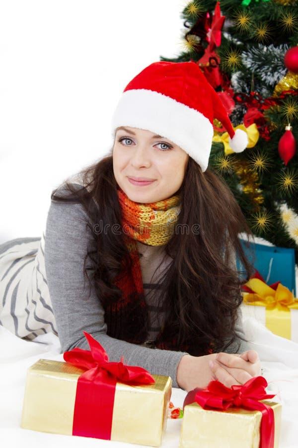 Kvinna i jultomtenhatten som ligger under julgranen royaltyfri foto