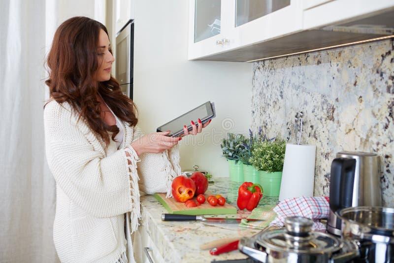 Kvinna i kök arkivfoton