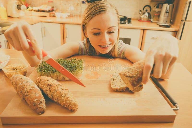 Kvinna i kökinnehavkniven som gör den sunda smörgåsen arkivbilder