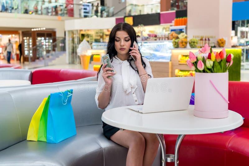 Kvinna i kafeteria med bärbara datorn, telefonen och dollar arkivfoto
