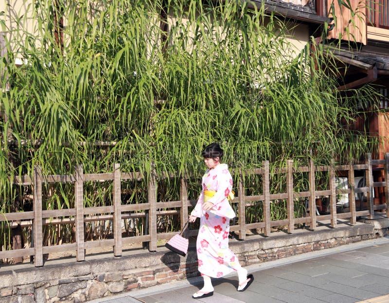 Kvinna i kimonoklänning som går på gångbana- och bakgrundsbambuträdet med trästaketet royaltyfria foton