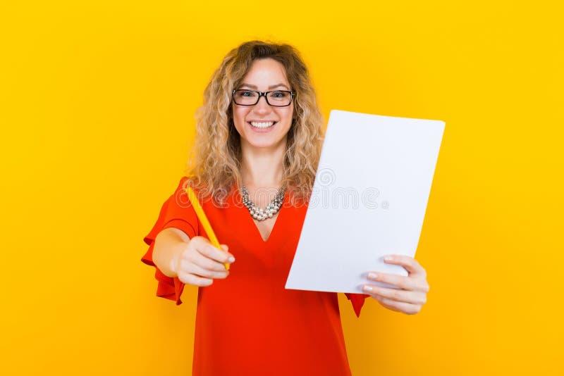 Kvinna i klänning med tomt papper och blyertspennan royaltyfri bild