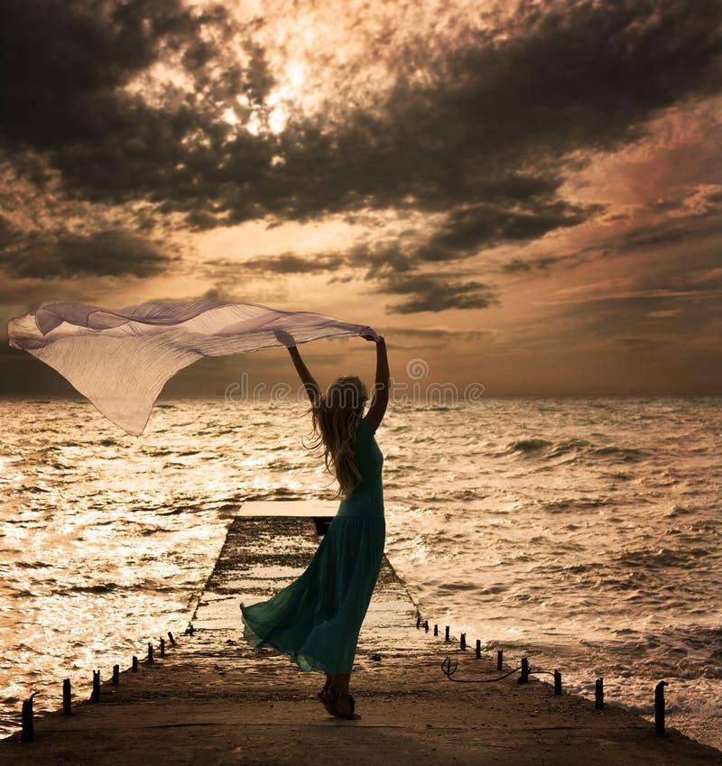 Kvinna i klänning med tyg på havet arkivbild