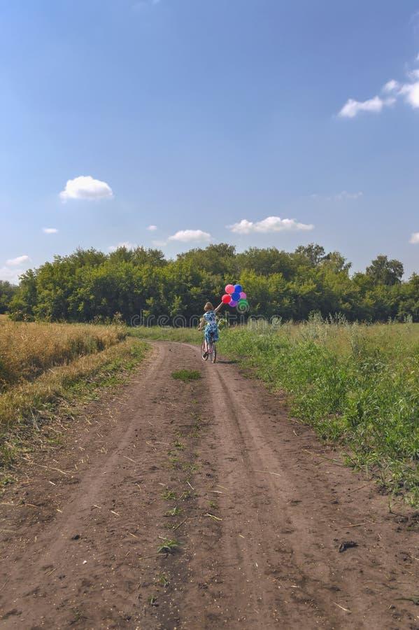 Kvinna i klänning på cykeln med färgrika ballonger arkivbilder