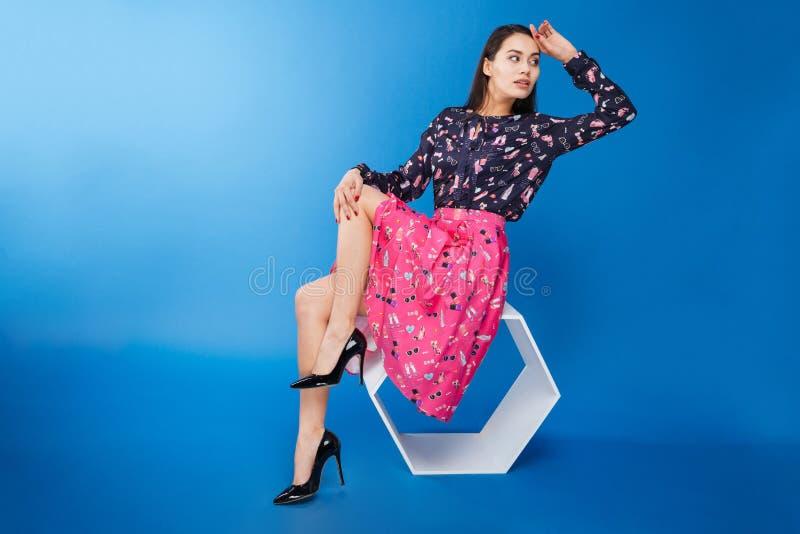 Kvinna i klänningsammanträde på modern stol royaltyfria foton