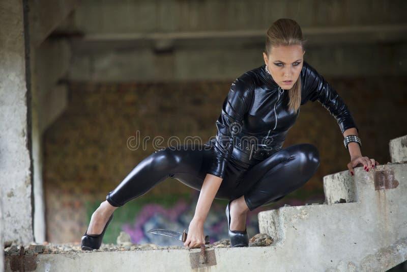 Kvinna i kniv för strid för läderklänninginnehav royaltyfri bild