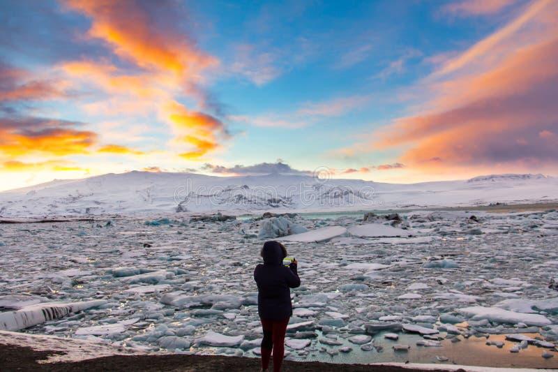 Kvinna i kontur som fotograferar glaciärlagun i Island royaltyfri bild