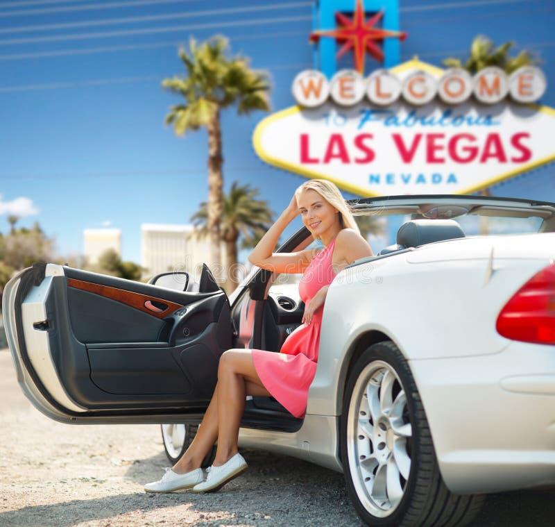 Kvinna i konvertibel bil över det Las Vegas tecknet arkivbilder