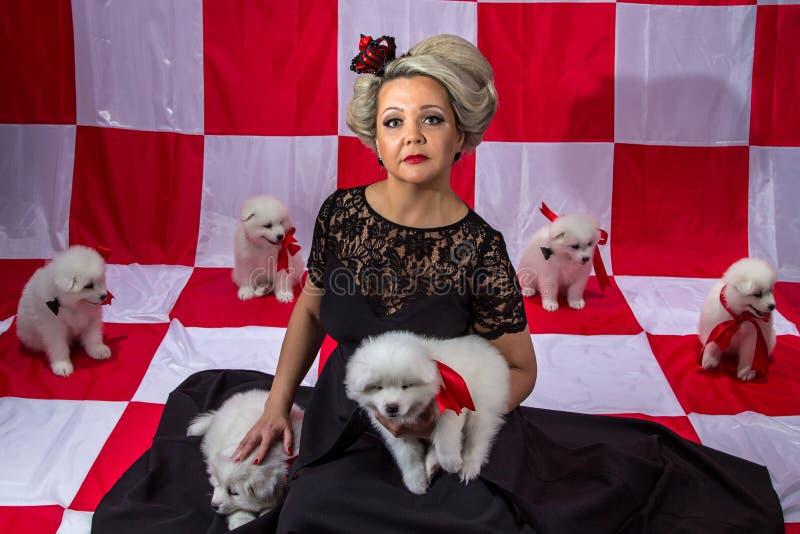 Kvinna i krona med vita valpar royaltyfria foton