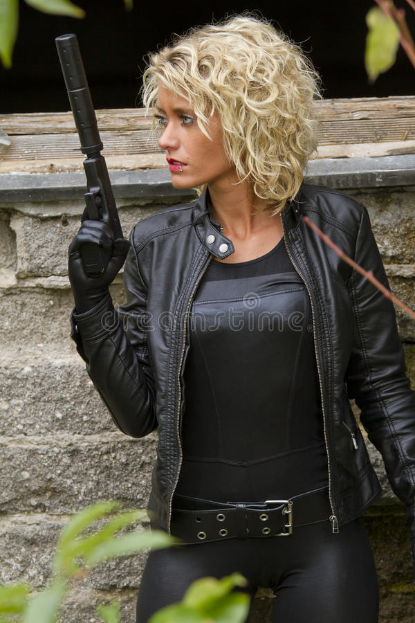 Kvinna i läder med ljuddämparetrycksprutan arkivfoton