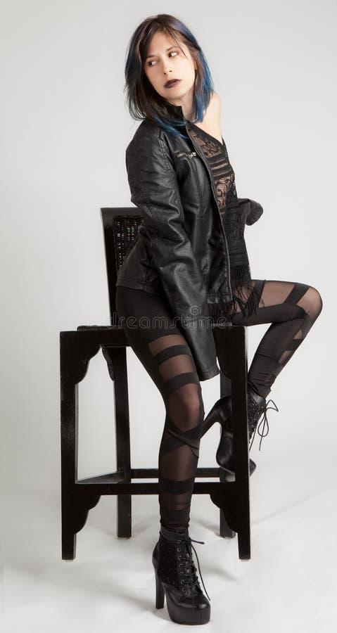 Kvinna i läderomslag och damasker på stol royaltyfri bild