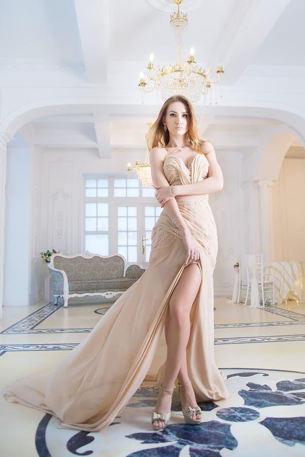 Kvinna i lång beige klänning i inre, lyx royaltyfria foton