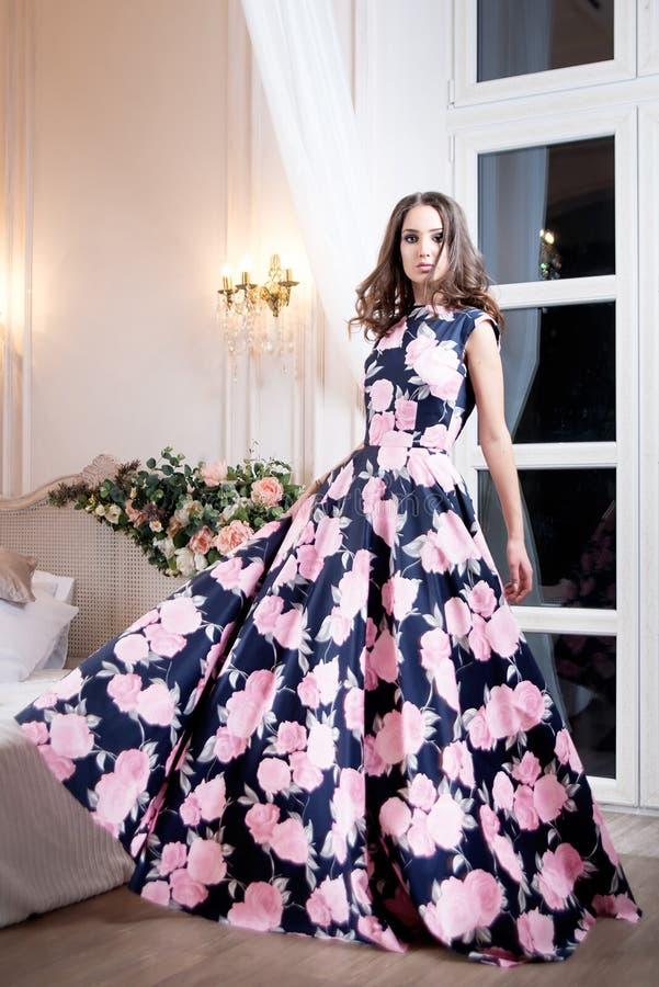 Kvinna i lång blom- klänning för elegans i studio Mode arkivbilder