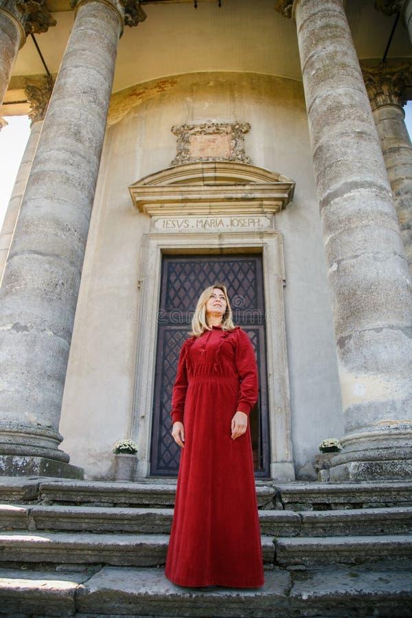 Kvinna i lång röd klänningställning på trappa royaltyfria bilder