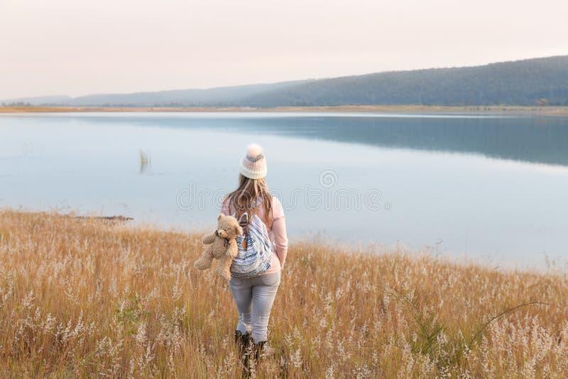Kvinna i långa mjuka gräs vid sjölandsliv arkivfoto